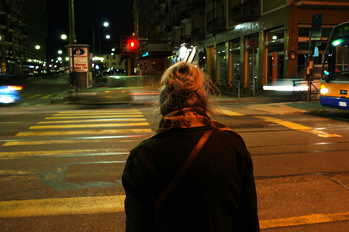 Elderly woman crossing city intersection.