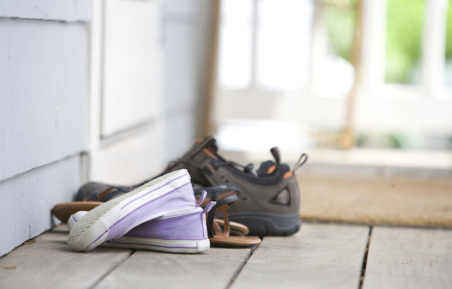 Pairs of shoes on a door mat from Public Health Image Library